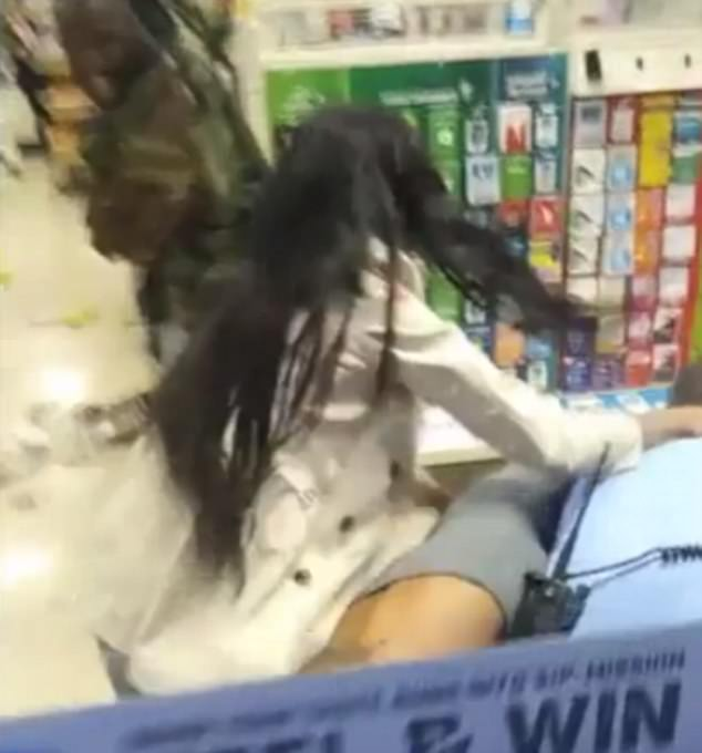 The other woman tries to intervene as the officer has her friend pinned to the ground