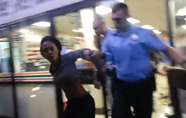 The woman yells as she is escorted from the store by an officer